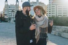Les couples de jeunes touristes, amis marchent le long de la rue de ville, buvant du café tandis qu'ils regardant heureusement l' Image libre de droits