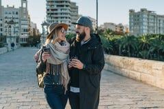 Les couples de jeunes touristes, amis marchent le long de la rue de ville, buvant du café tandis qu'ils regardant heureusement l' Image stock