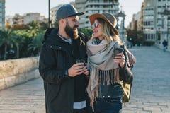 Les couples de jeunes touristes, amis marchent le long de la rue de ville, buvant du café tandis qu'ils regardant heureusement l' Images libres de droits