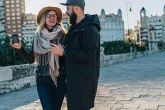 Les couples de jeunes touristes, amis marchent le long de la rue de ville, buvant du café tandis qu'ils regardant heureusement l' Photographie stock libre de droits