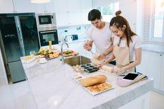 Les couples de l'adolescence asiatiques aident à faire le dîner Photo libre de droits