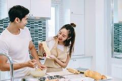Les couples de l'adolescence asiatiques aident à faire le dîner Image libre de droits
