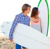 Les couples de l'adolescence de surfer sur la plage étayent avec des planches de surf Photographie stock