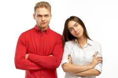 Les couples de la femelle blonde de mâle et de brune, bras ont croisé et avec les visages contrariés regardant en avant photo libre de droits