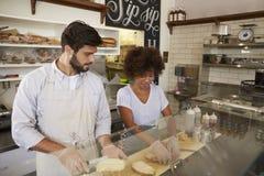 Les couples de métis fonctionnent derrière le compteur à une barre de sandwich images stock