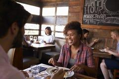 Les couples de métis prenant le déjeuner dans le restaurant occupé, se ferment  Photos libres de droits