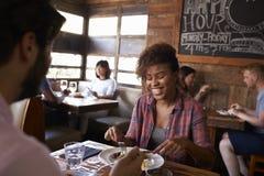 Les couples de métis prenant le déjeuner dans le restaurant occupé, se ferment  Photo libre de droits