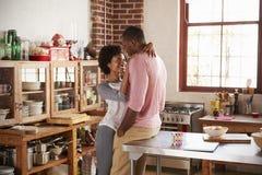 Les couples de métis reposent l'embrassement dans la cuisine Photo libre de droits