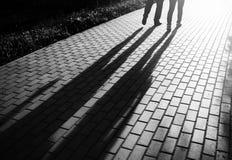 Les couples de marche noirs et blancs dans le coucher du soleil garent le contexte de bokeh Photo libre de droits
