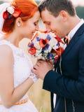 Les couples de mariage dans l'amour apprécient un moment de bonheur et regardent affectueusement l'un l'autre sur le champ de blé Photo stock