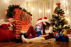 Les couples de Noël dans l'amour dans des chapeaux Santa Claus lisant un livre Photographie stock