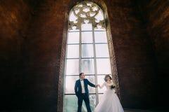 Les couples de nouveaux mariés posant devant la vieille cathédrale gothique ont arqué la fenêtre avec le filigrane Photos stock