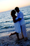 les couples de plage silhouettent le mariage images stock