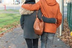 les couples de retour ont enlacé la marche dans la rue par automne image stock