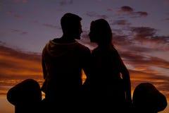 Les couples de silhouette se reposent sur le parement de banc Photographie stock