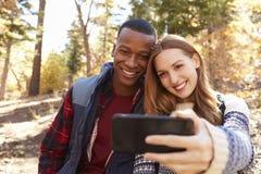 Les couples de sourire de métis prennent un selfie dans une forêt Photographie stock libre de droits