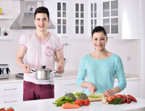 Les couples de sourire mangent de la salade dans la cuisine Photographie stock
