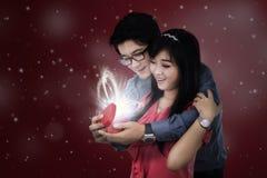 Les couples de sourire ouvrent un cadeau Photographie stock
