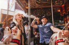 Les couples de sourire sur le carrousel de cheval montent au champ de foire Photo libre de droits