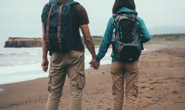 Les couples de voyageur dans l'amour marchant sur la mer échouent Images stock