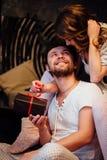 Les couples dedans dans des pyjamas se reposant sur le plancher à côté du lit et se donnent des cadeaux dans des boîtes Image libre de droits