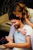 Les couples dedans dans des pyjamas se reposant sur le plancher à côté du lit et se donnent des cadeaux dans des boîtes Images libres de droits