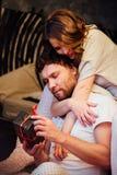 Les couples dedans dans des pyjamas se reposant sur le plancher à côté du lit et se donnent des cadeaux dans des boîtes Photos libres de droits