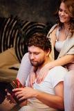 Les couples dedans dans des pyjamas se reposant sur le plancher à côté du lit et se donnent des cadeaux dans des boîtes Photographie stock libre de droits