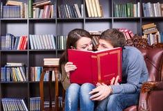 Les couples derrière un livre se regardant se sont ainsi fermés Photos libres de droits