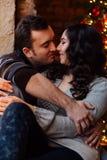 Les couples des étreintes d'amants se reposant sur le rebord de fenêtre dans Noël tracent le studio le type étreint la fille Images libres de droits