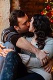 Les couples des étreintes d'amants se reposant sur le rebord de fenêtre dans Noël tracent le studio le type étreint la fille Images stock