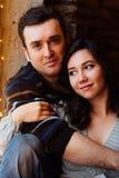 Les couples des étreintes d'amants se reposant sur le rebord de fenêtre dans Noël tracent le studio le type étreint la fille Photos libres de droits