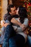 Les couples des étreintes d'amants se reposant sur le rebord de fenêtre dans Noël tracent le studio le type étreint la fille Image libre de droits