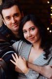 Les couples des étreintes d'amants se reposant sur le rebord de fenêtre dans Noël tracent le studio le type étreint la fille Image stock