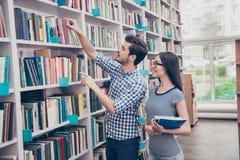 Les couples des étudiants internationaux sont dans la bibliothèque ensemble à l'arrière Photographie stock
