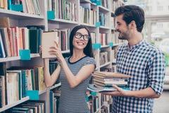 Les couples des étudiants internationaux sont dans la bibliothèque ensemble à l'arrière Photographie stock libre de droits
