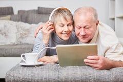 Les couples des aînés écoutent la musique avec le comprimé Photo libre de droits