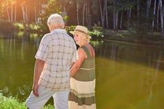 Les couples des aînés s'approchent du lac Photo stock