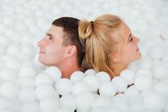 Les couples des amis affectueux ont l'amusement entourés par les boules en plastique blanches dans une piscine sèche Image stock