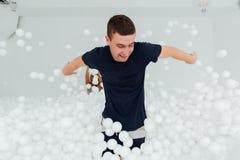 Les couples des amis affectueux ont l'amusement entourés par les boules en plastique blanches dans une piscine sèche Photo libre de droits