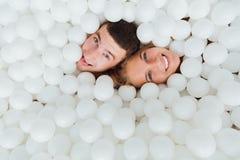 Les couples des amis affectueux ont l'amusement entourés par les boules en plastique blanches dans une piscine sèche Images libres de droits