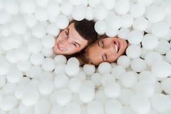 Les couples des amis affectueux ont l'amusement entourés par les boules en plastique blanches dans une piscine sèche Images stock