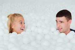 Les couples des amis affectueux ont l'amusement entourés par les boules en plastique blanches dans une piscine sèche Photo stock