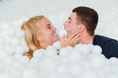 Les couples des amis affectueux ont l'amusement entourés par les boules en plastique blanches dans une piscine sèche Photographie stock libre de droits