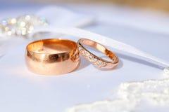 Les couples des bagues à diamant de mariage d'or sur le mariage blanc se reposent Photographie stock