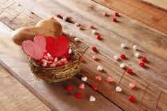 Les couples des coeurs rouges dans l'oiseau nichent sur la table en bois Photo libre de droits