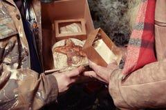 Les couples des hommes sans abri en hiver garent célébrer seul Noël avec le cadeau de pain Images stock