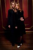 Les couples des jeunes blonds se sont habillés dans le noir dans une chambre noire Photo stock