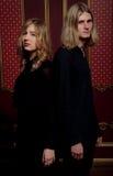 Les couples des jeunes blonds se sont habillés dans le noir dans une chambre noire Photos stock