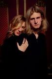 Les couples des jeunes blonds se sont habillés dans le noir dans une chambre noire Photographie stock